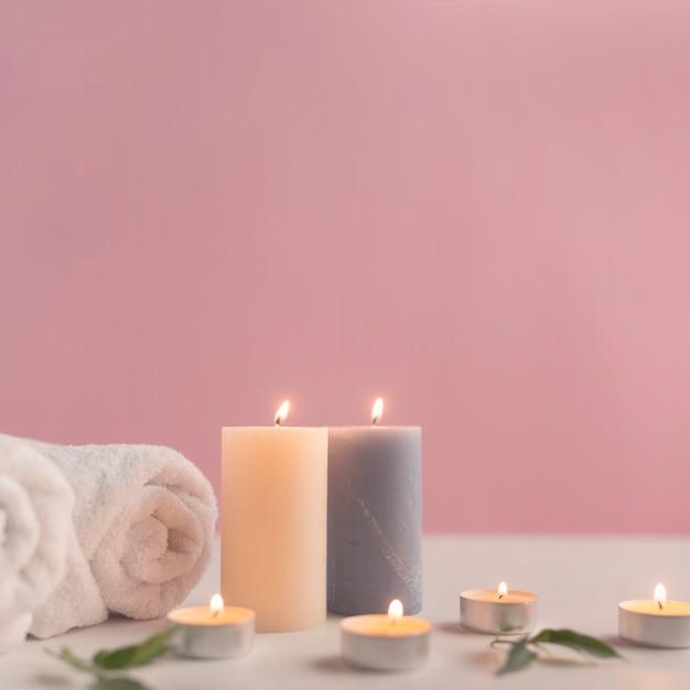 Asciugamano arrotolato con candele accese su sfondo rosa Foto Gratuite