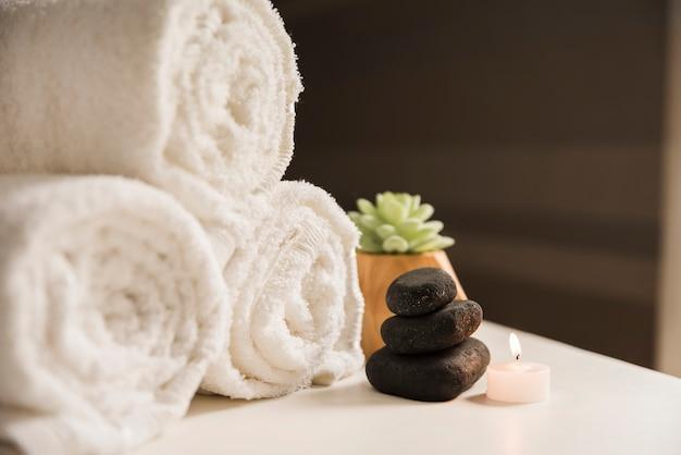 Asciugamano arrotolato con pietra spa e candela illuminata sul tavolo Foto Gratuite