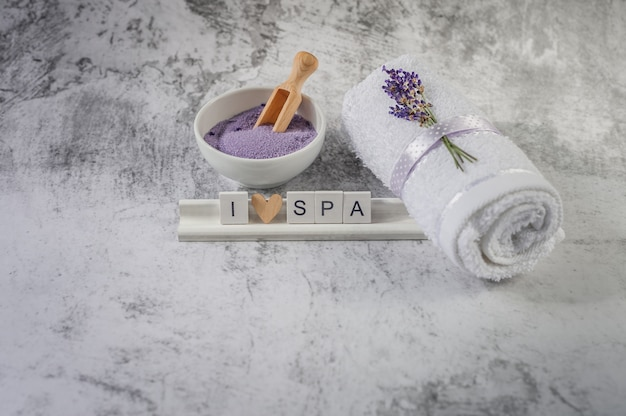 Asciugamano da bagno contorto con lavanda e ortografia di lettere in legno Foto Premium