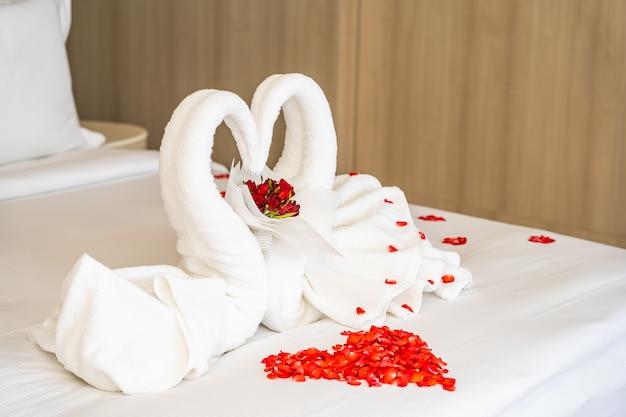 Asciugamano del cigno sul letto con i petali del fiore della rosa rossa Foto Gratuite