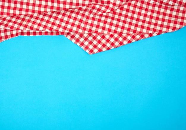 Asciugamano di cucina a quadretti rosso bianco su un fondo blu, fondo luminoso di picnic Foto Premium