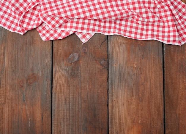 Asciugamano di cucina a quadretti rosso bianco su una tavola di legno marrone Foto Premium
