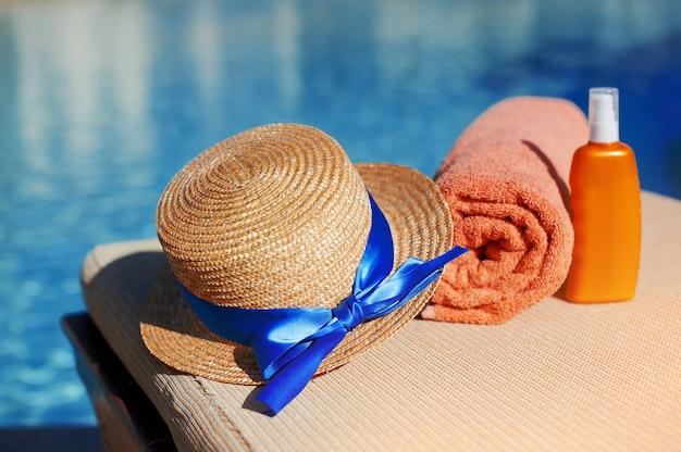 Asciugamano in cotone arancione e crema solare per il corpo e cappello in un tubo arancione Foto Premium