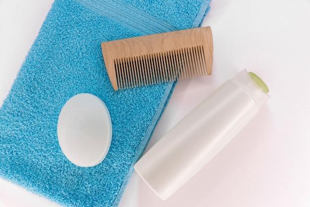 Asciugamano, sapone, shampoo e pettine su uno sfondo bianco. Foto Premium