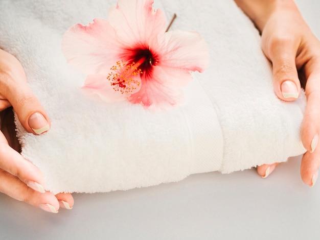 Asciugamano tenuto in mano con un fiore in cima Foto Gratuite
