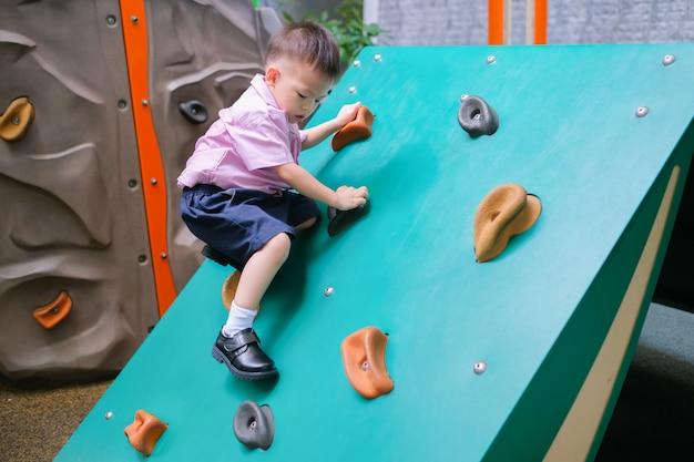 Asian 2 - 3 anni bambino bambino divertirsi cercando di arrampicarsi su massi artificiali nel cortile della scuola, ragazzino arrampicata su parete di roccia Foto Premium