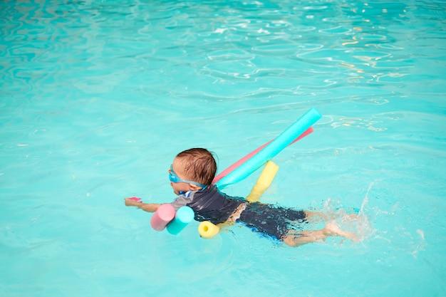 Asian 2 - 3 anni bambino ragazzo bambino prendere lezioni di nuoto, il bambino impara a galleggiare con la tagliatella da solo, scherza tenendo il giocattolo e calciare le gambe nella piscina coperta Foto Premium
