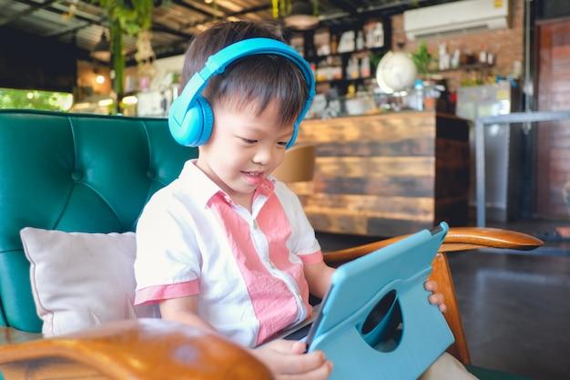 Asiatici 3-4 anni bambino ragazzo bambino sorridente mentre era seduto in poltrona utilizzando il computer tablet pc Foto Premium
