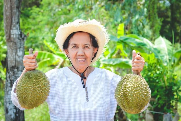 Asiatici contadini anziani che indossano cappelli, con in mano 2 frutti di durian Foto Premium