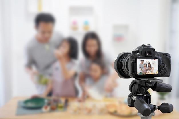 Asiatico felice della famiglia che fa una macchina fotografica digitale di video blogger di vlog con la cottura nella stanza della cucina Foto Premium