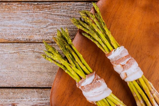 Asparago verde avvolto con pancetta sul piatto di legno. Foto Premium