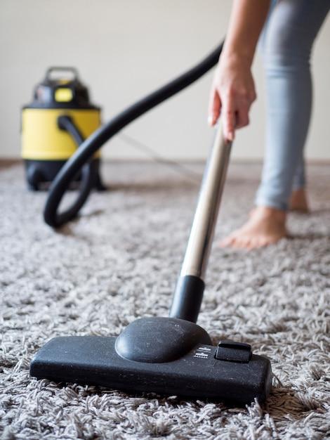 Aspirapolvere del primo piano che pulisce la moquette Foto Gratuite