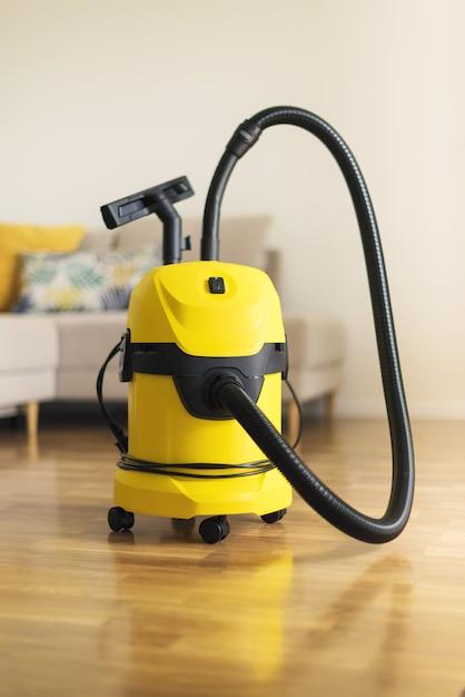 Aspirapolvere moderno giallo in salotto. copia spazio concetto di aspirazione a fondo piatto Foto Premium