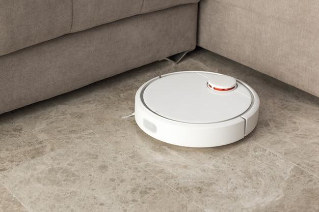 Aspirapolvere robot che pulisce la stanza Foto Premium