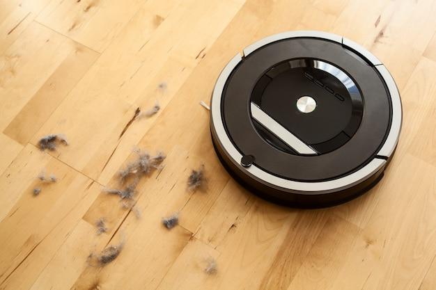 Aspirapolvere robotico su polvere di tecnologia di pulizia intelligente del pavimento in legno laminato Foto Premium