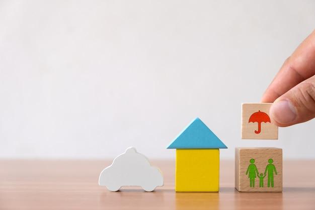 Assicurazione e concetto di investimento di salute, vita, infortunio e viaggi. scelto a mano blocco di legno con tema assicurativo, casa, famiglia, auto Foto Premium