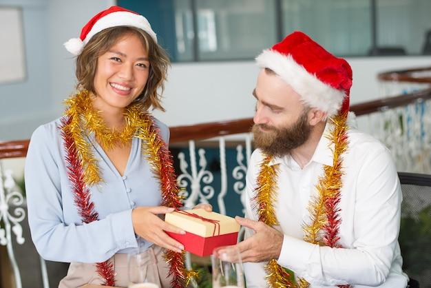 Assistente di ufficio allegro in cappello della santa che dà il regalo di natale Foto Gratuite