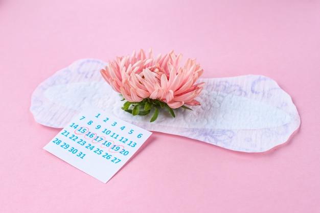 Assorbenti femminili e sanitari per giorni critici e un fiore rosa. cura dell'igiene durante le mestruazioni. ciclo mestruale regolare. protezione mensile Foto Premium