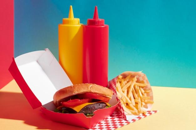 Assortimento alimentare con hamburger e bottiglie di salsa Foto Gratuite