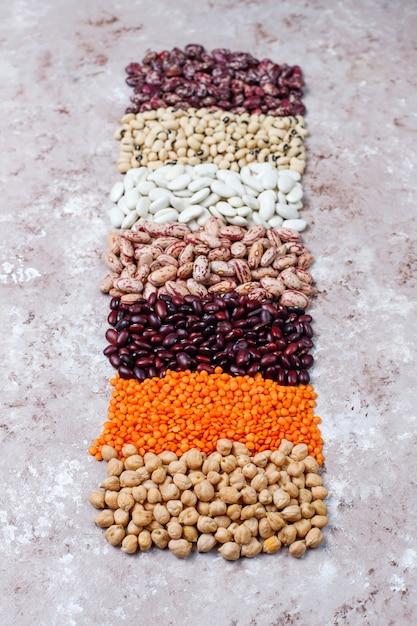 Assortimento di legumi e fagioli in diverse ciotole su fondo in pietra chiara. vista dall'alto. alimento proteico vegano sano. Foto Gratuite