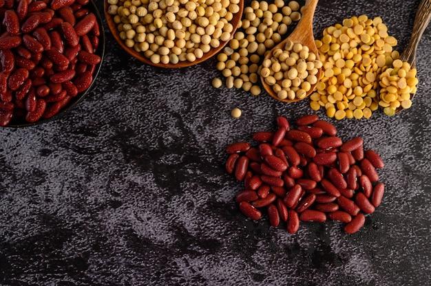 Assortimento di legumi e fagioli sul pavimento di cemento nero. Foto Gratuite