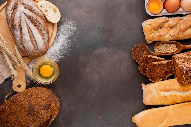 Assortimento di pane con uovo e sfondo con texture Foto Gratuite