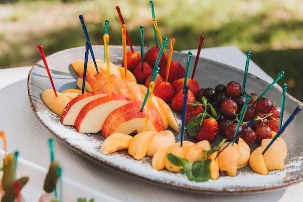 Assortimento di snack di frutta o finger food offerti agli ospiti a un ricevimento di matrimonio o una festa da parte della società di catering Foto Premium