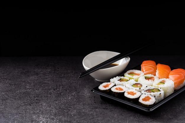 Assortimento di sushi sul vassoio nero e salsa di soia copyspace Foto Premium