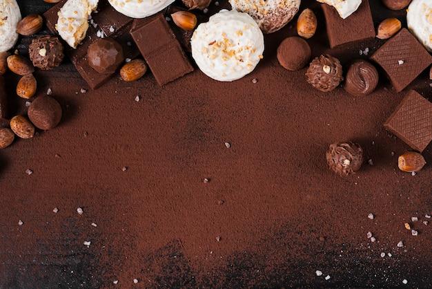 Assortimento e cacao in polvere piani dei dolci del cioccolato su fondo rosa con lo spazio della copia Foto Gratuite