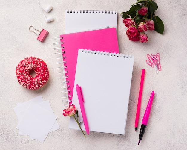 Assortimento su quaderni con ciambella e bouquet di rose Foto Gratuite