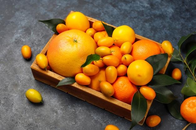 Assortiti agrumi freschi nel cestello per la conservazione degli alimenti, limoni, arance, mandarini, kumquat, pompelmo, vista dall'alto Foto Gratuite