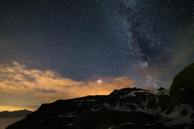 Astro cielo notturno, via lattea stelle sopra le alpi, cielo tempestoso, pianeta marte oltre le nuvole, catena montuosa innevata Foto Premium
