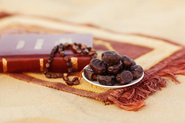 Вates e rosari, splendidamente disposti sul tappeto da preghiera nel deserto. Foto Premium