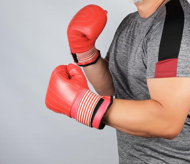 Atleta adulto muscoloso in uniforme grigia e guantoni da boxe in pelle rossa Foto Premium