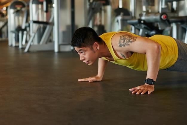 Atleta asiatico facendo flessioni in una palestra Foto Gratuite