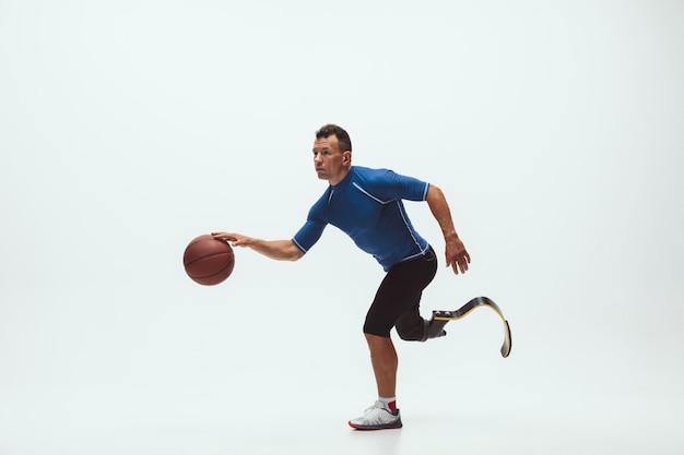 Atleta con disabilità o amputato isolato sullo spazio bianco dello studio. giocatore di pallacanestro maschio professionale con l'addestramento della protesi della gamba e la pratica nello studio. Foto Gratuite