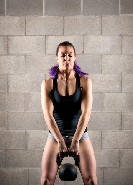 Atleta della ragazza che si esercita con un kettlebell Foto Premium