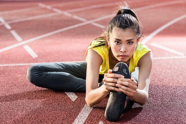 Atleta donna che si estende sulla pista da corsa prima di correre Foto Premium