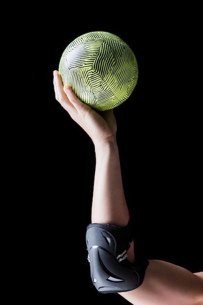 Atleta femminile con la pallamano della tenuta del cuscinetto di gomito sul nero Foto Premium