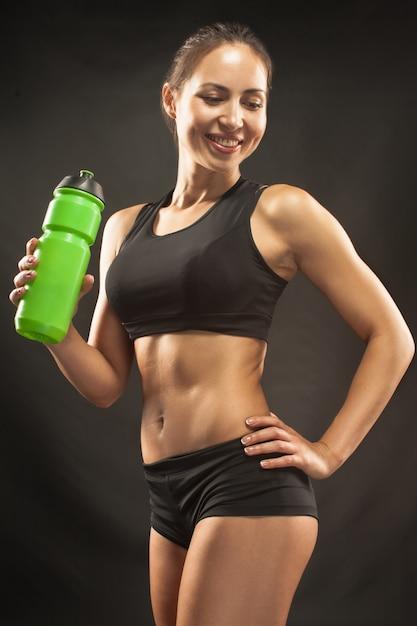 Atleta muscolare della giovane donna con un'acqua sul nero Foto Gratuite