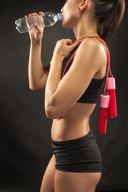 Atleta muscolare della giovane donna con una corda per saltare sul nero Foto Gratuite