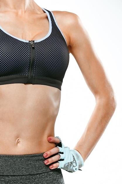 Atleta muscolare della giovane donna su bianco Foto Gratuite