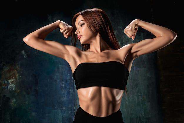 Atleta muscolare della giovane donna sul nero Foto Gratuite