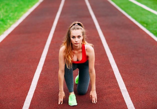 Atletica donna in pista iniziando a correre. concetto di fitness sano con stile di vita attivo. Foto Premium