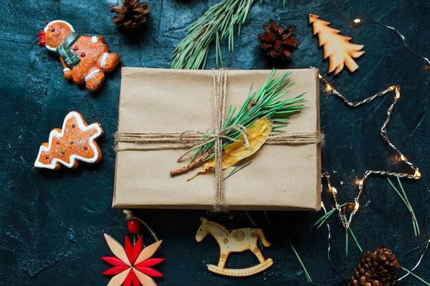 Atmosfera di capodanno regalo di capodanno e portacandele accanto all'albero di natale e giocattoli di natale su sfondo scuro Foto Premium