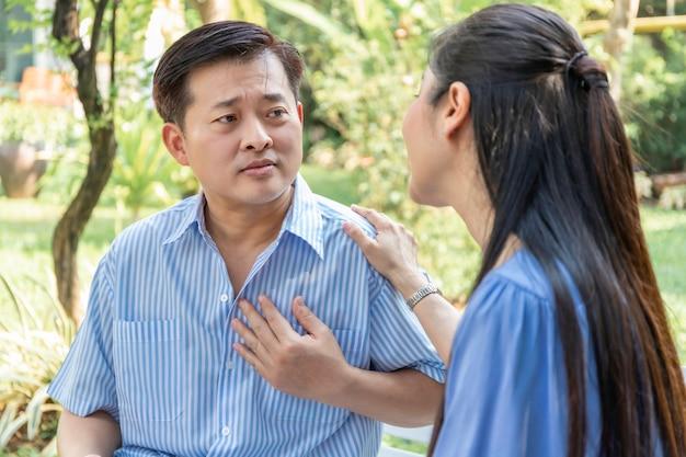 Attacco di cuore asiatico dell'uomo senior durante il rilassamento con la moglie al parco. Foto Premium