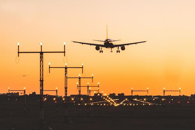 Atterraggio di aeroplano al tramonto, silhouette Foto Premium