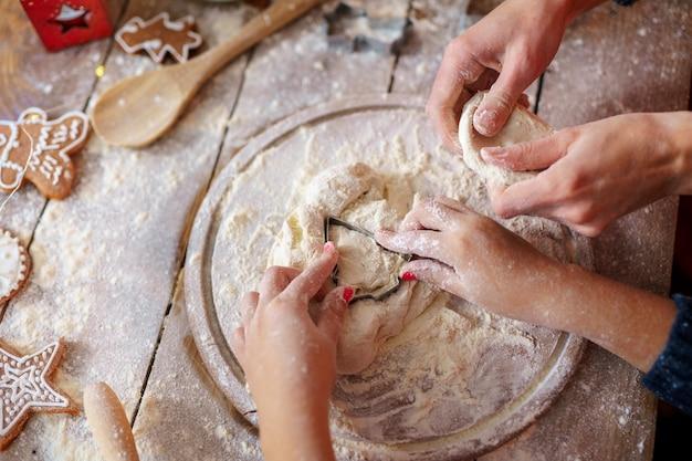 Attività per le vacanze in famiglia. vista superiore delle mani del bambino e della madre che producono i biscotti dell'albero di natale sul fondo di legno della tavola. flat lay. Foto Premium