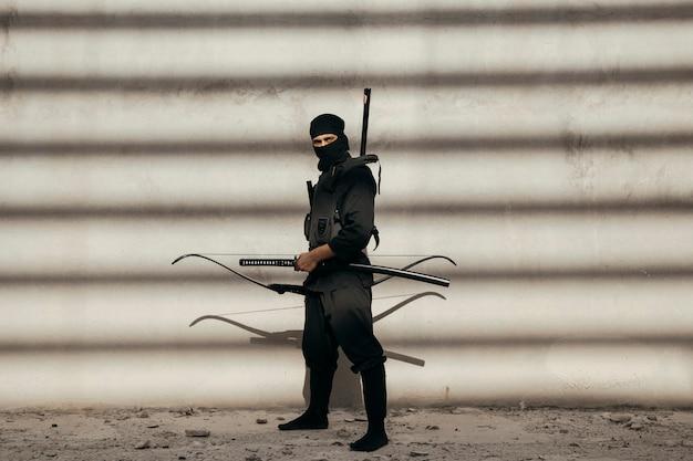 Attore che svolge il ruolo di arciere in maschera e abiti Foto Gratuite