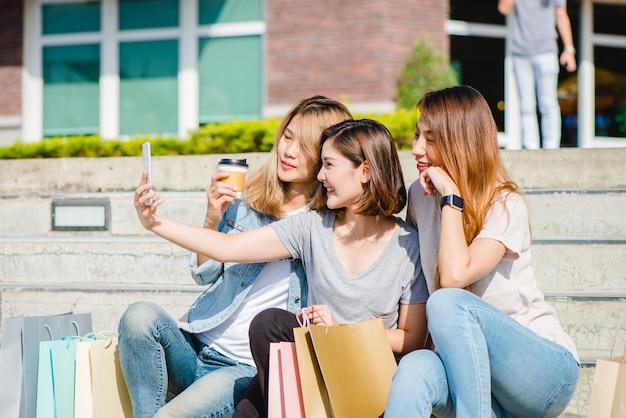 Attraente bella donna asiatica utilizzando uno smartphone mentre lo shopping in città Foto Gratuite